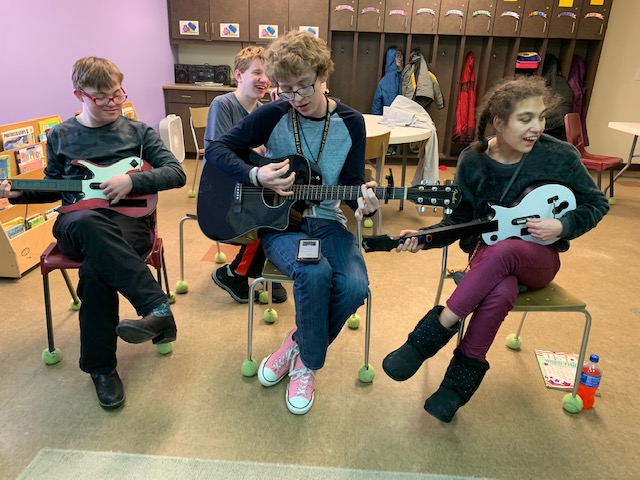 Daycare participants play guitars during a music activity.