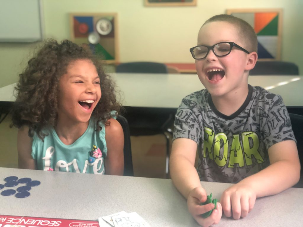 Two children laughing while doing an activity.